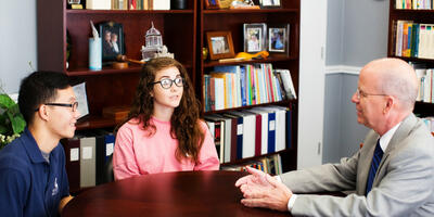 Two students sit at a brown round table and talk to President Dr. Ken Shaw