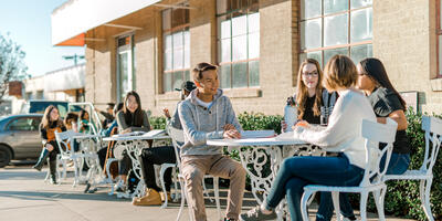 Outside several students are sitting with their friends at the metal tables and chairs outside of the Student Center
