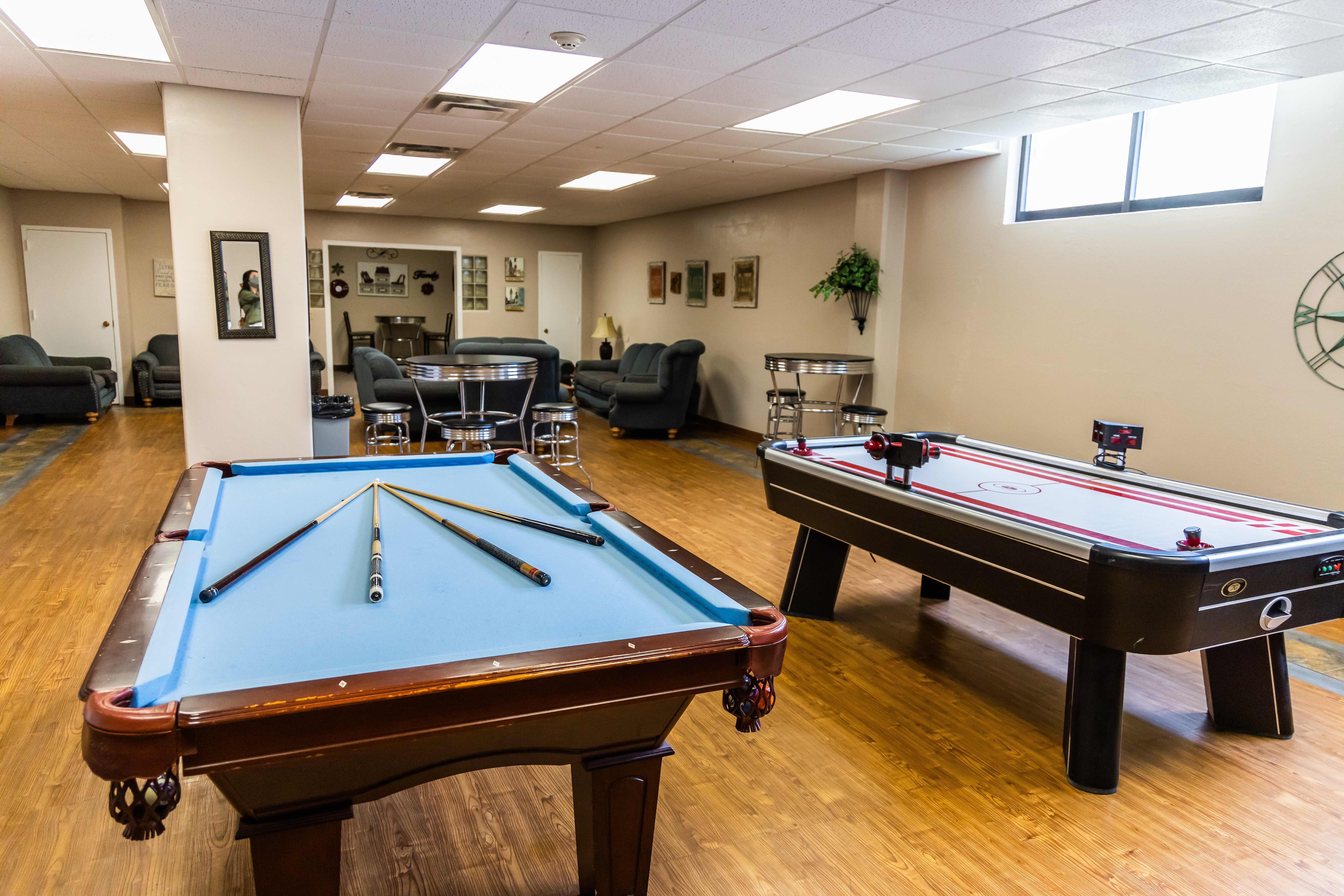 A game room with a pool table, air hockey table and various couches for seating