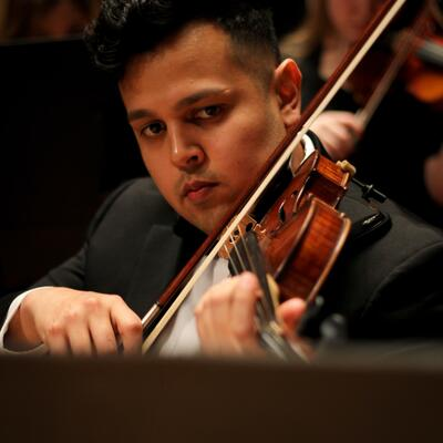 A male, with short black hair, reads his music while his violin sits between his chin and shoulder as he plays
