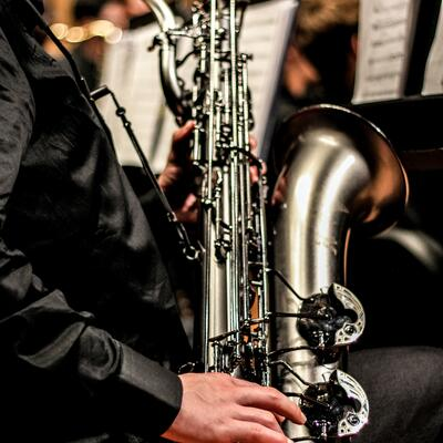 A young man, wearing all black, holds his silver saxophone to the side as he begins to play