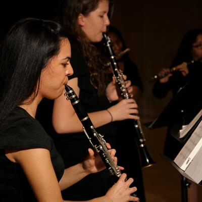 A clarinet player, with medium-lengthed dark hair, holds and plays her insturment while reading her music
