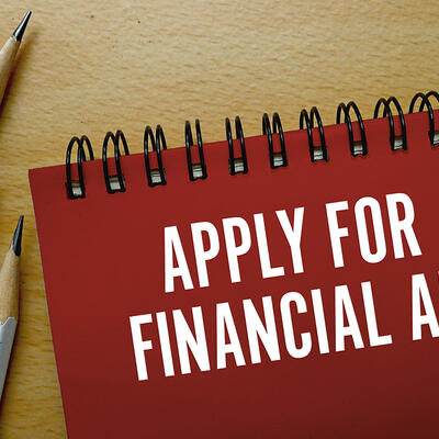 Written in white words on a red notebook, a note encourages students to apply for financial aid
