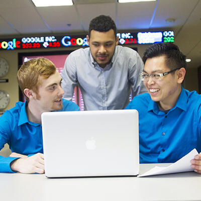 Three students sit around a laptop as they discuss their business strategy