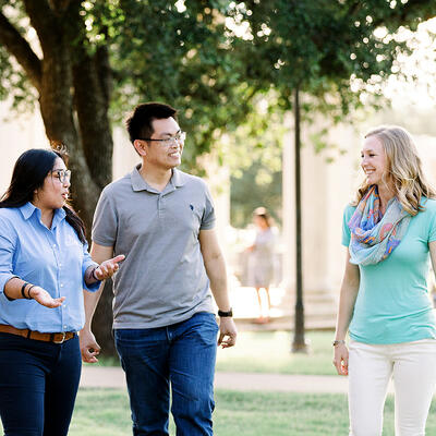 While walking through campus, small groups of alumn smile as they talk outside
