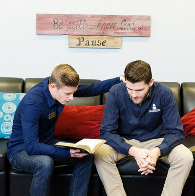 A male staff, wearing jeans and a blue button up, holds a bible and prays with a student, wearing khakis and a SWAU-labeled button up