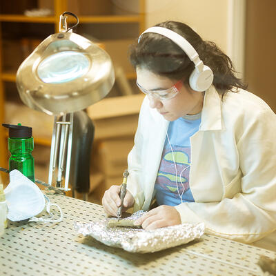 A student, wearing a lab coat, protective glasses, and headphones carefully uses a tool to clean a fossil or bone