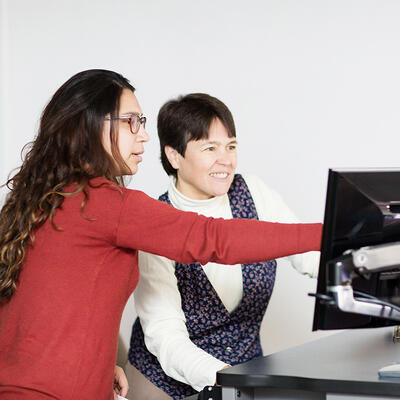 A student points to a computer as she shows the professor something about class