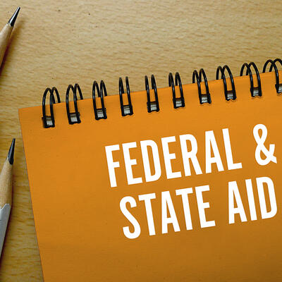 """The cover of an orange notepad says """" Federal and State Aid"""" in white words"""