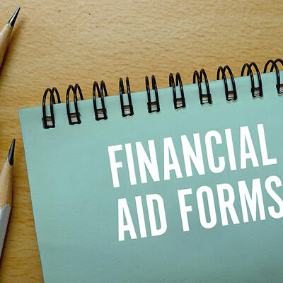 """The cover of a teal notepad says """"Financial Aid Forms"""" in white words"""
