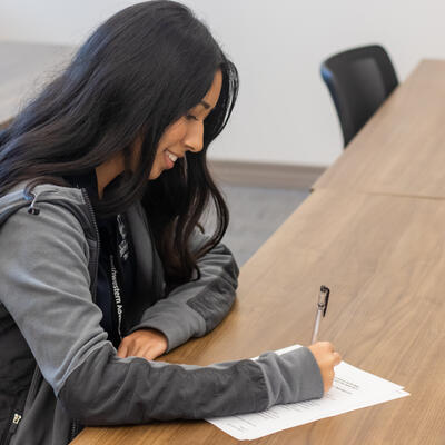 A student wearing a jacket smiles as she looks down and begins to take her test
