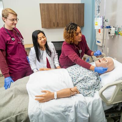 A nursing student, dressed in maroon scrubs, places oxygen tubes in a fake patients nose while a peer and professor stand by and watch