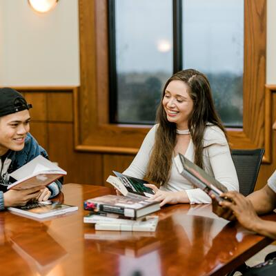 Three students sit together in a table in pechero smiling and looking through books