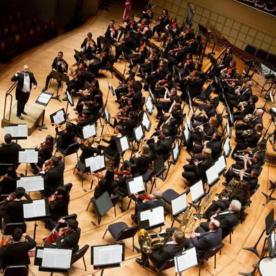 Birdview shot of an symphony orchestra filled with brass instruments, wood and percussion sitting in several semi-circles with the conductor in the front