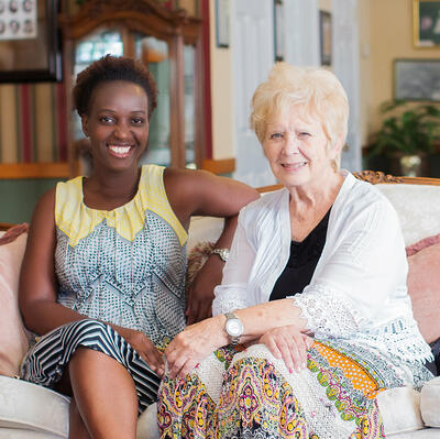 Sitting on a white couch and chair, three women look forward and smile