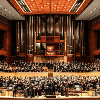 A mass choir with women in black gowns and men in all black suits stand in rows in front of a huge organ