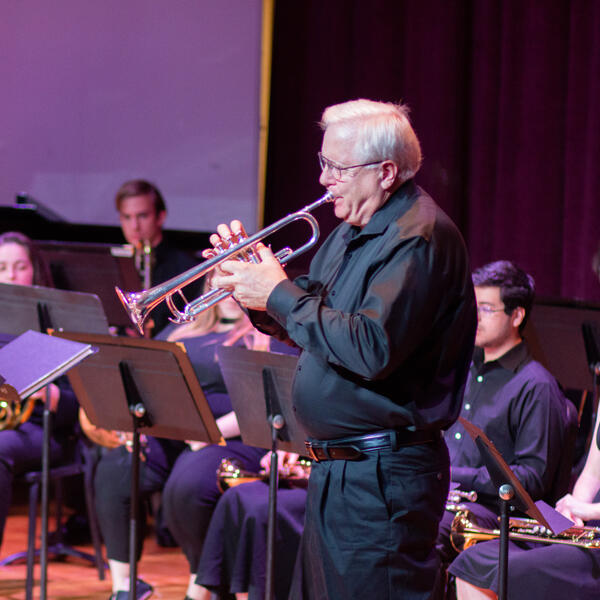 Professor with grey hair and glasses, playing goldeen trumpet at a university recital.
