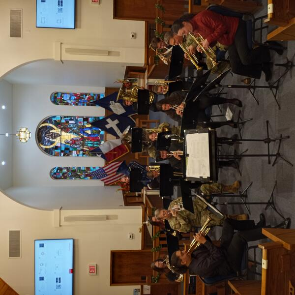 Brass ensemble playing with soldiers at Camp Mabry