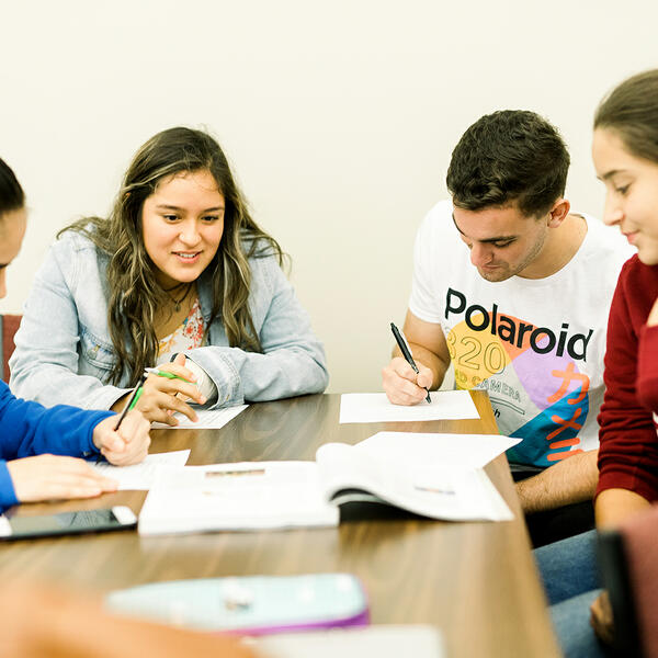 Four students sit together at a table and do assignments and study together
