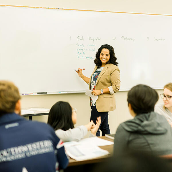 A business professor smiles and turns from writing on her board as she listens to a students question