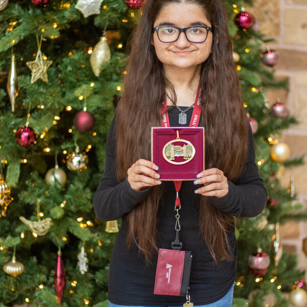 Caroline Torres poses in front of a Christmas tree holding a box containing the Mizpah ornament