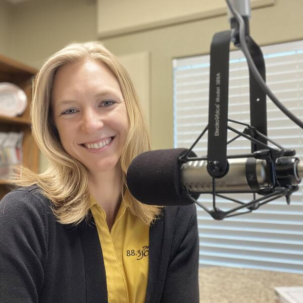 Danae Songy in a yellow 88.3 The Journey shirt in front of a radio mic