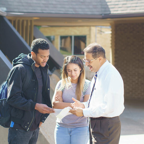 A female and a male student talking with Professor Rico, in front of Barron Chapel, as they read a note card.