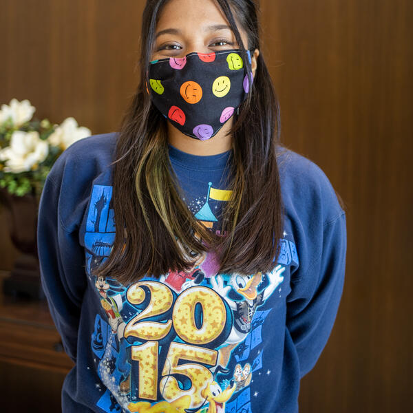 Genesis Santos poses for the camera in a mask with cartoon smiling faces and a blue sweatshirt