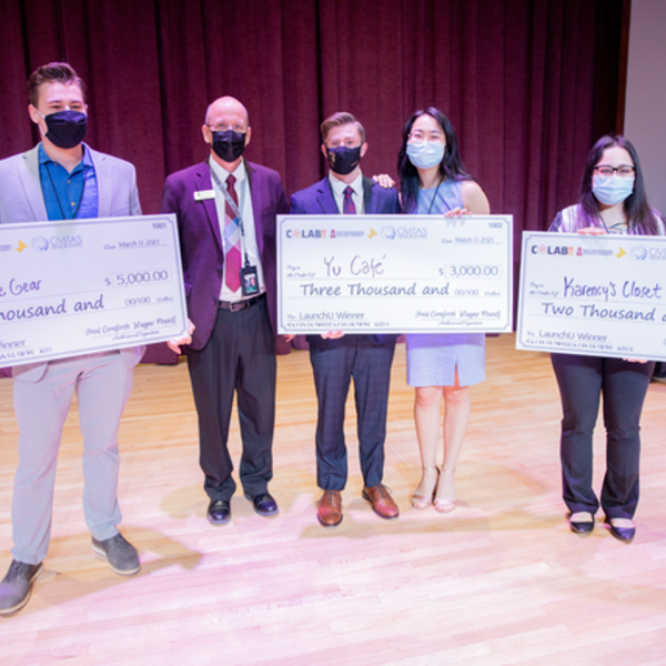 Dr. Shaw stands with the winners of the LaunchU competition who are all holding large checks that say the amount of money they have won