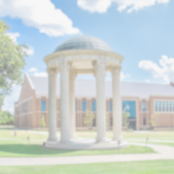 A blurred photo of the university campus showcasing the nursing building, rotunda and the beautiful green grade in between the sidewalks