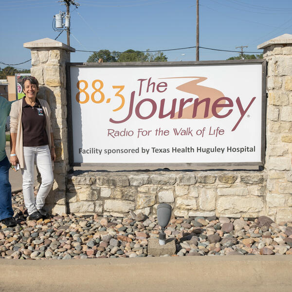 """Mike and Wanda Agee stand to the left of the radio station sign that reads """"88.3 The Journey, Radio for the Walk of Life."""" Danae stands to the right of the sign."""
