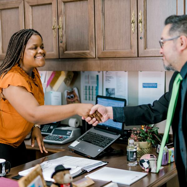 A female stands up from behind her desk and smiles as she leans forward to shake the hand of a gentleman standing on the other side of her desk
