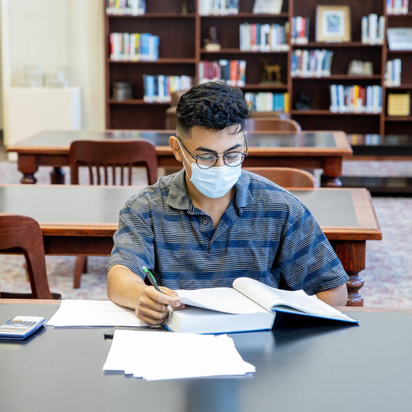 Student wearing a mask sits at a table in the library in front of an open textbook