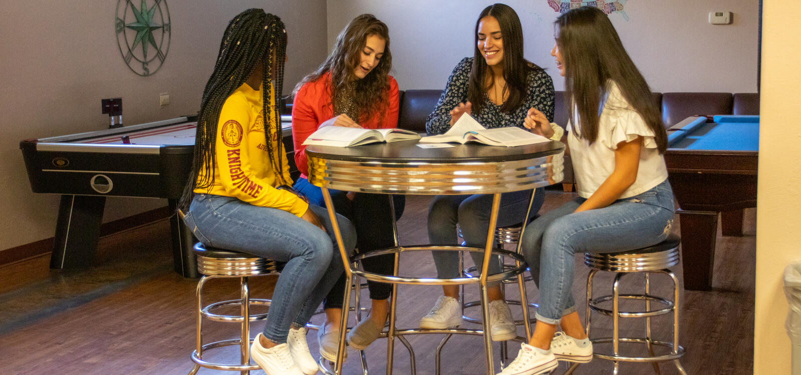Four students sit at a small round table and look through their textbooks together.