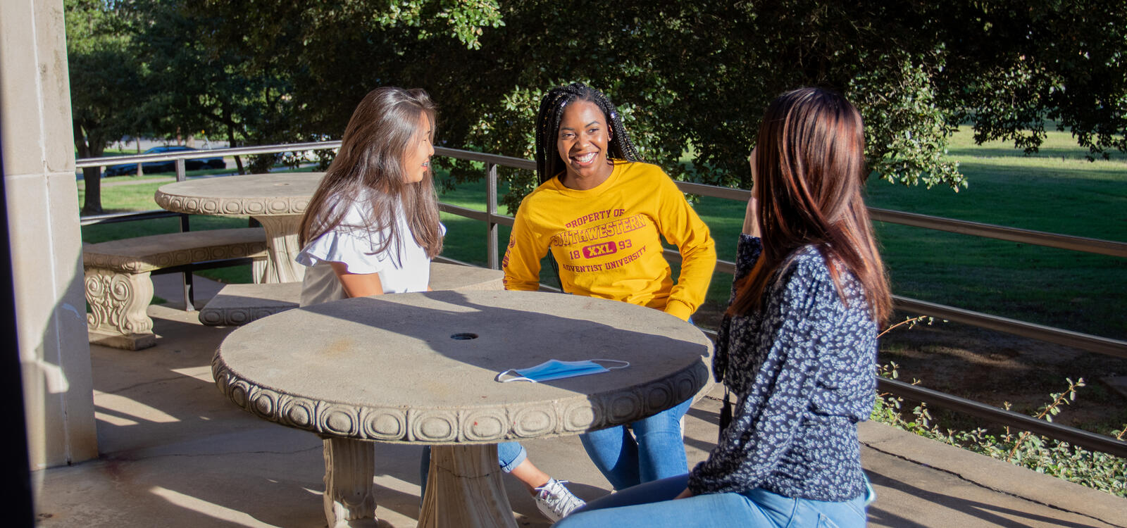 Three female students sit on the patio in the sunny weather and laugh