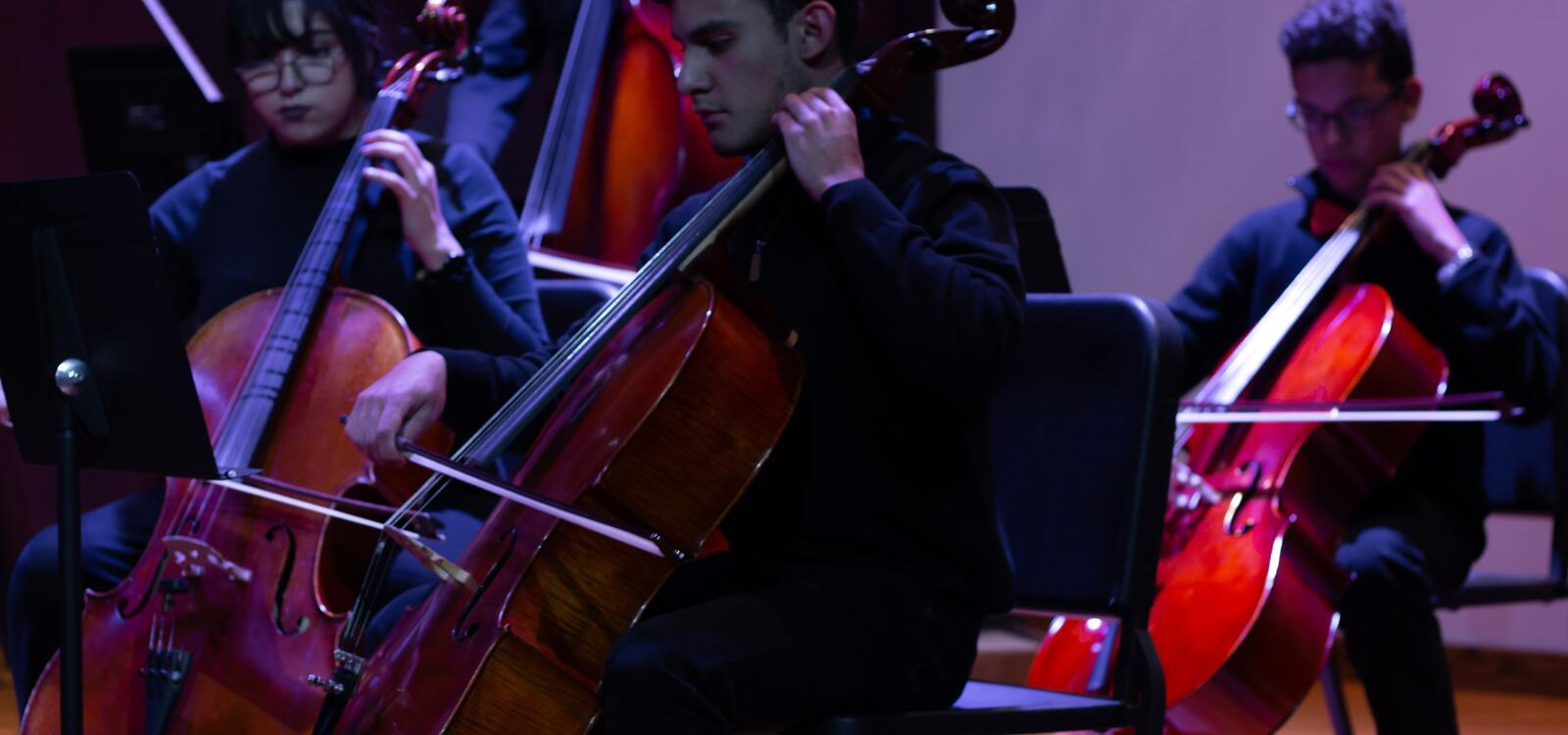 Three students sitting in chairs read their music as they play their cellos
