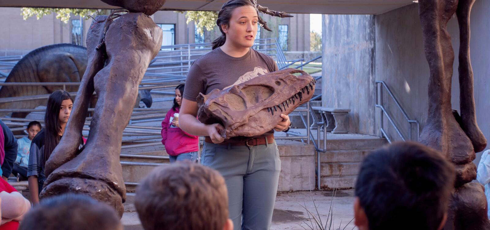 A dinosaur museum worker talks to the audience of children as she explains the dinosaur skull in her hands