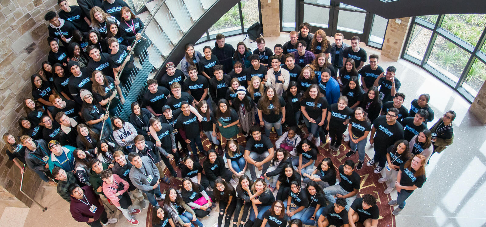 """A group of students, all matching in black shirts that say """"Southwestern Adventist University"""" in blue letters, look up as the stand on stairs and on the floor, smiling and looking up"""