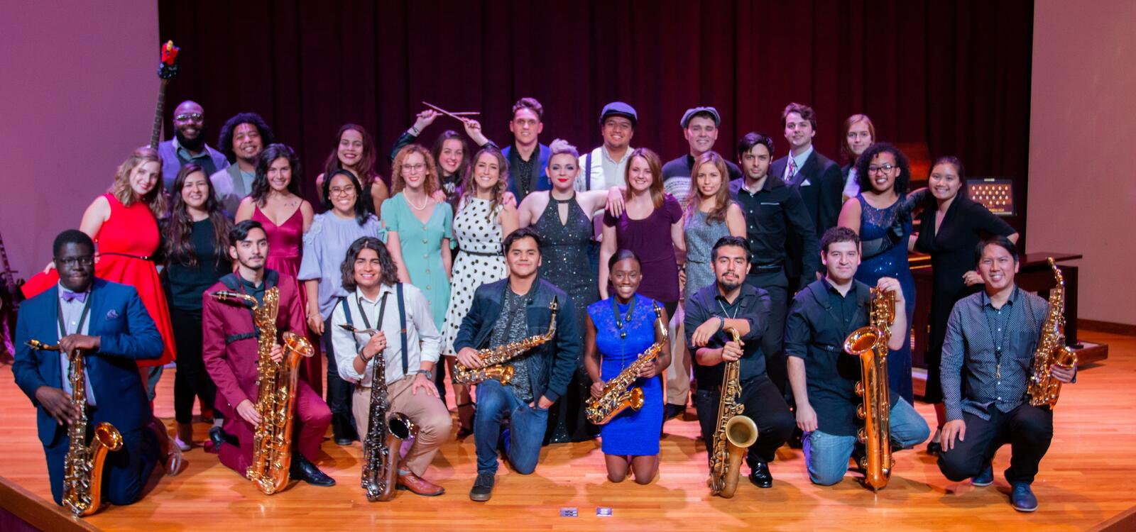 A group of students smile in three rows after they complete the SWAU recitals
