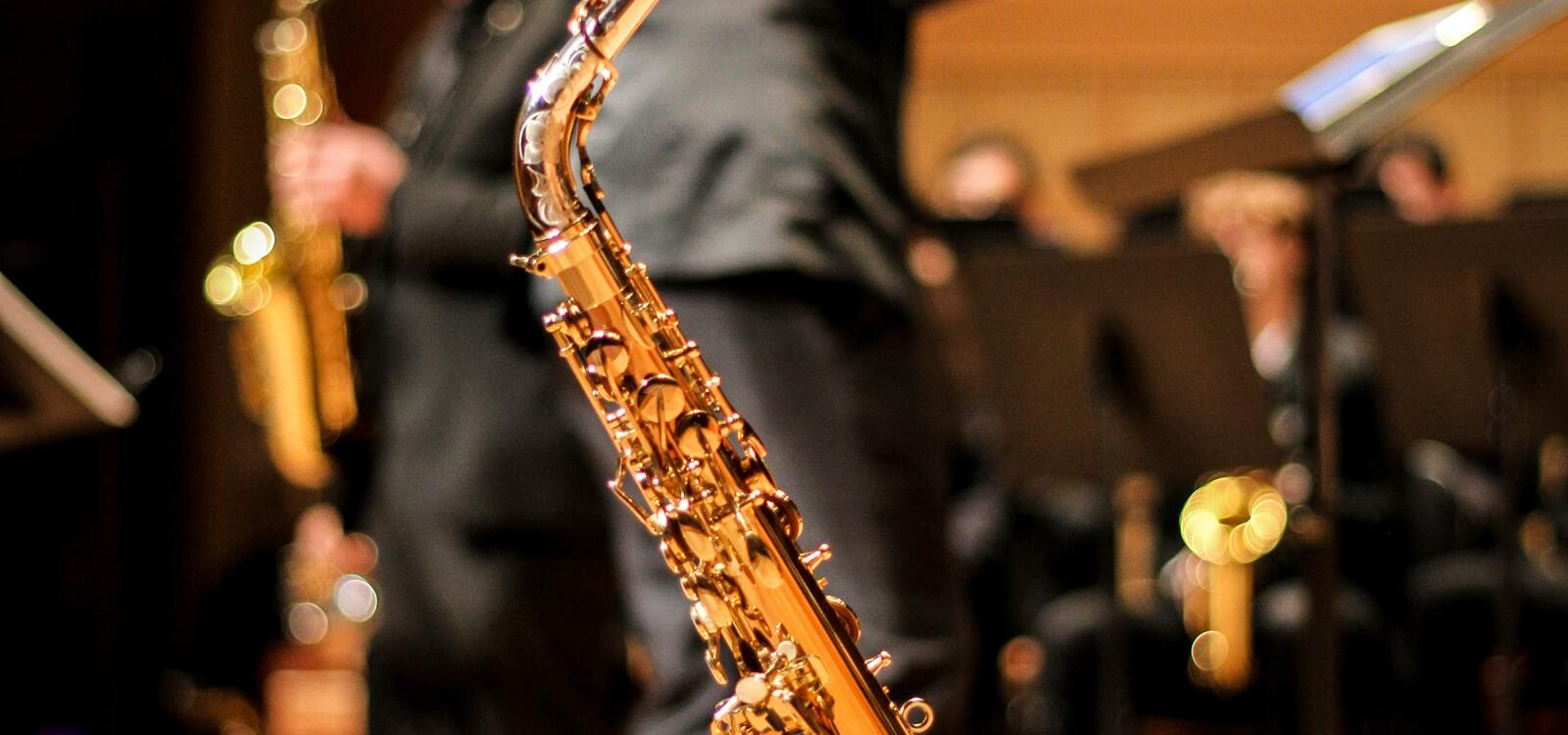 A photo of a shiny saxophone, and in the background a conducter is leading an ensemble