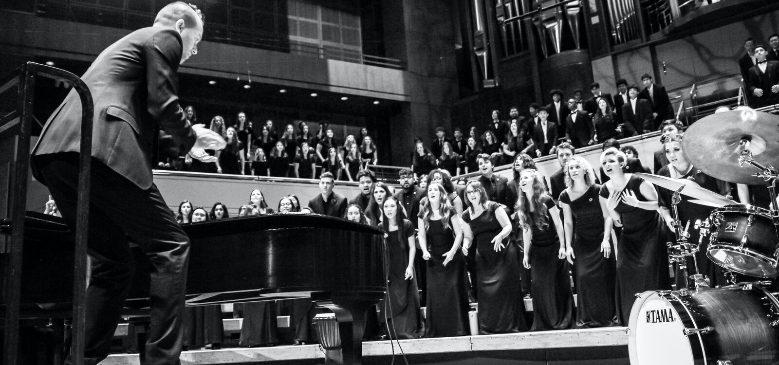 The choir, dressed in black, lean forward as they sing and follow the director who is also crouched down a bit