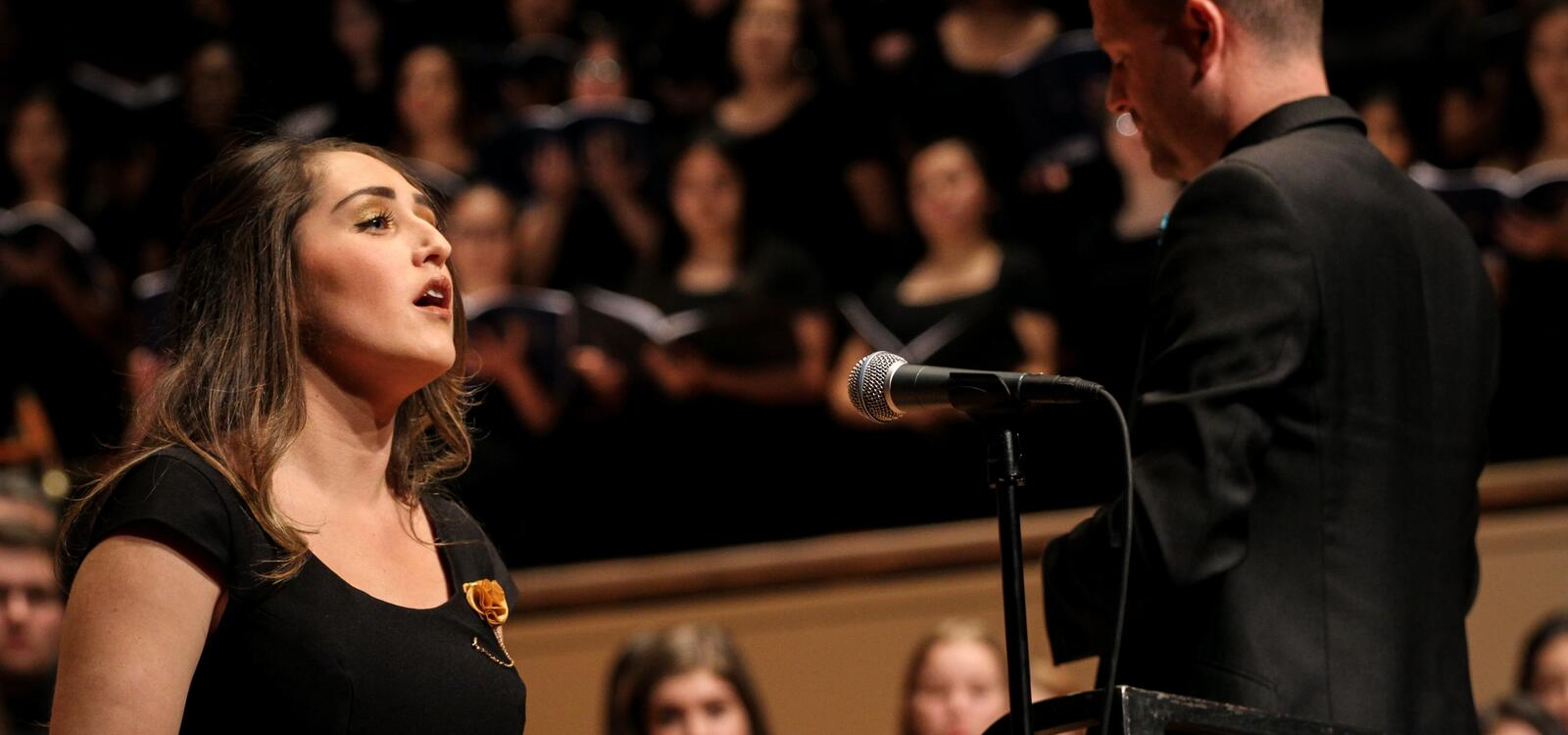 A female student stand in a black gown as she sings in fron of a mic. Her director can be seen beside her and the choir blurred behind her.