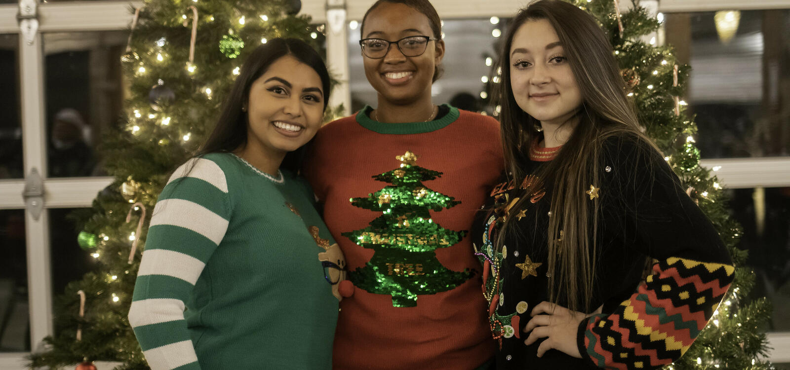 Three young ladies smiling, wearing red and greenn Christmas sweaters, standing together in front of two decorated Christmas trees with their arms around eachother
