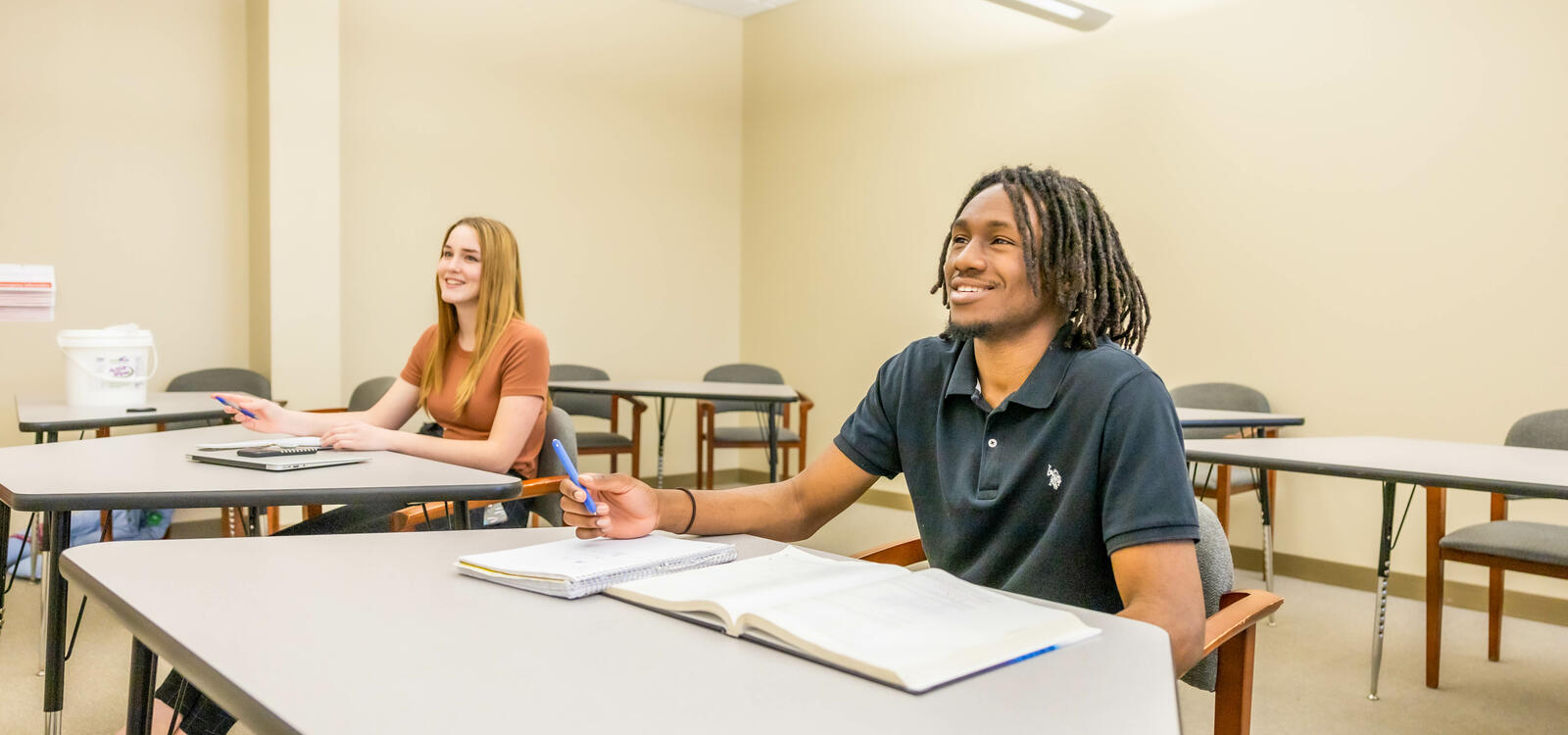 Two students sitting at desks smiling and listening attentively to the lecture.