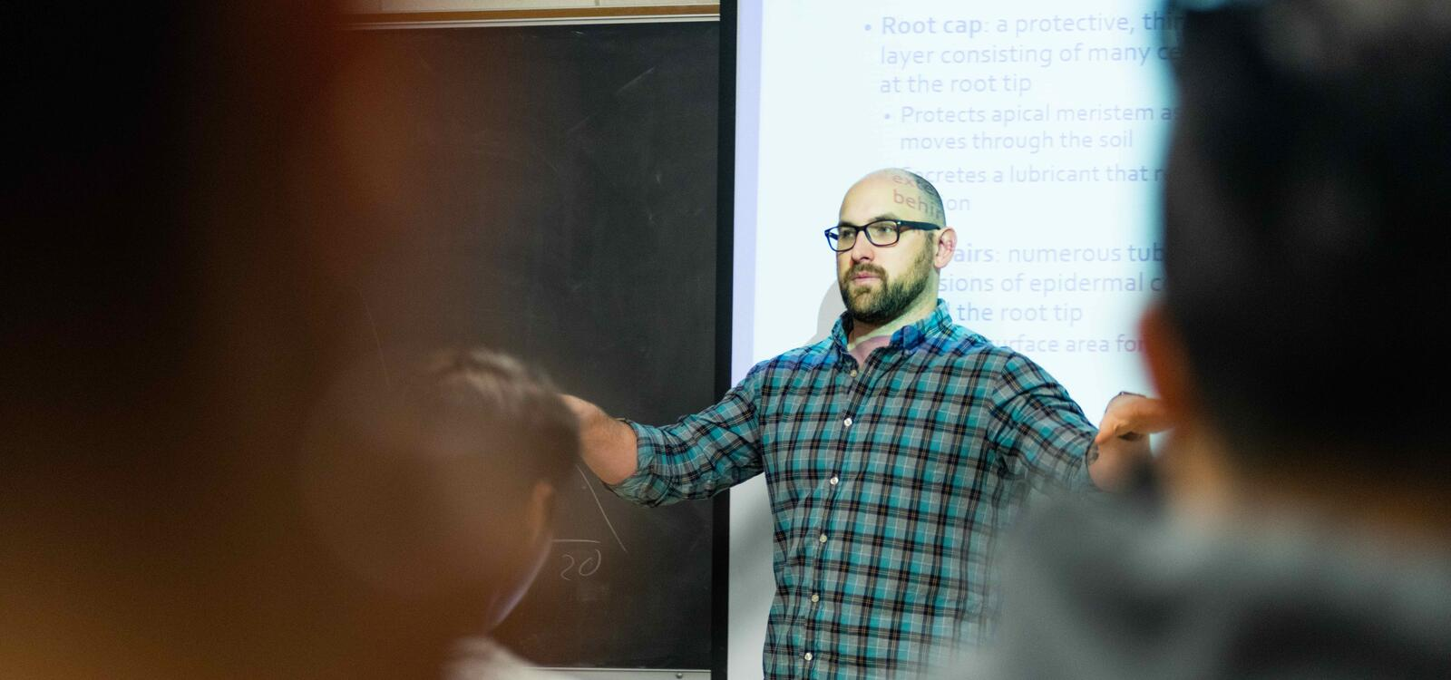 A biology professor stands in front of his projected slides and speaks to his class