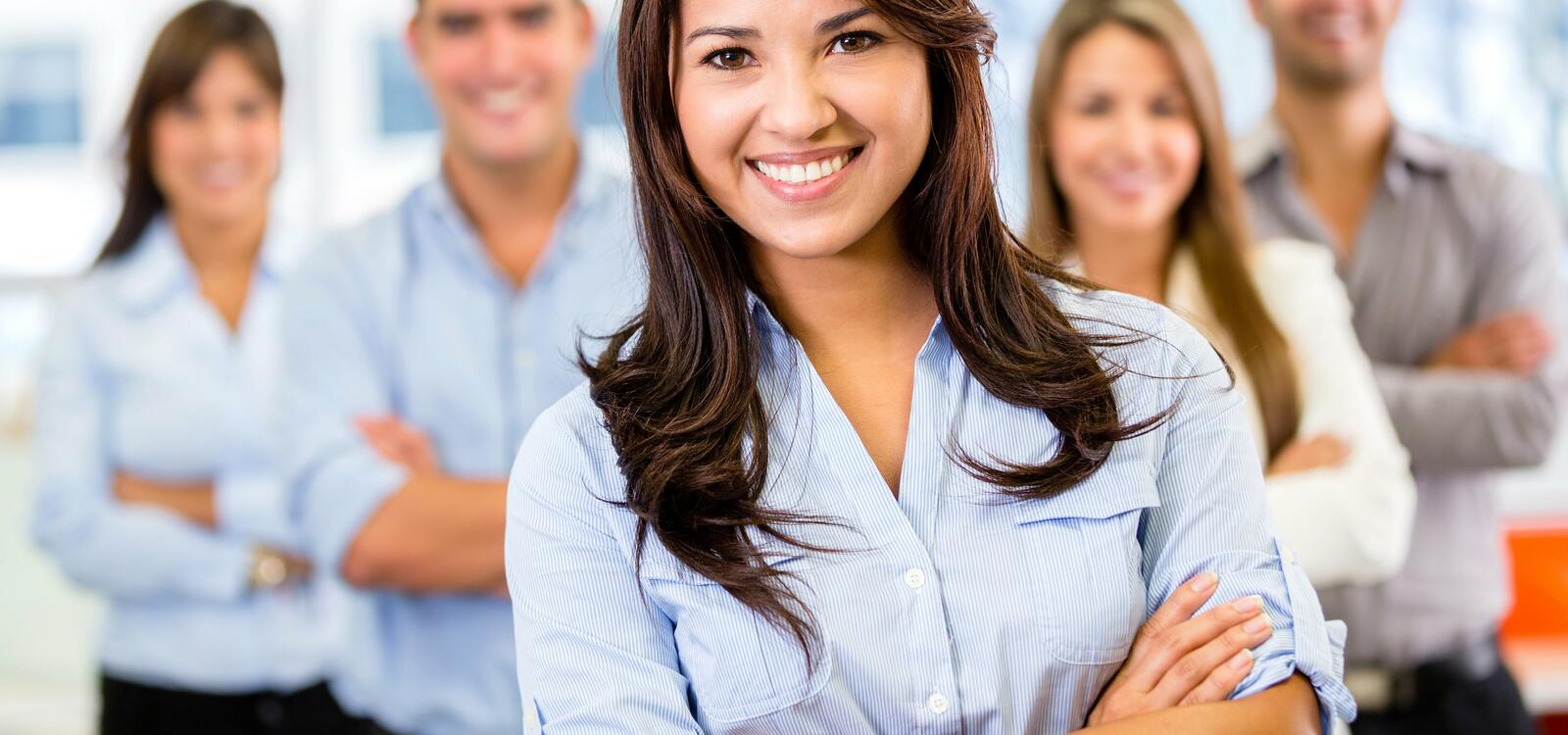 A woman crosses her arms in front of her and smiles as she stands in front of her peers