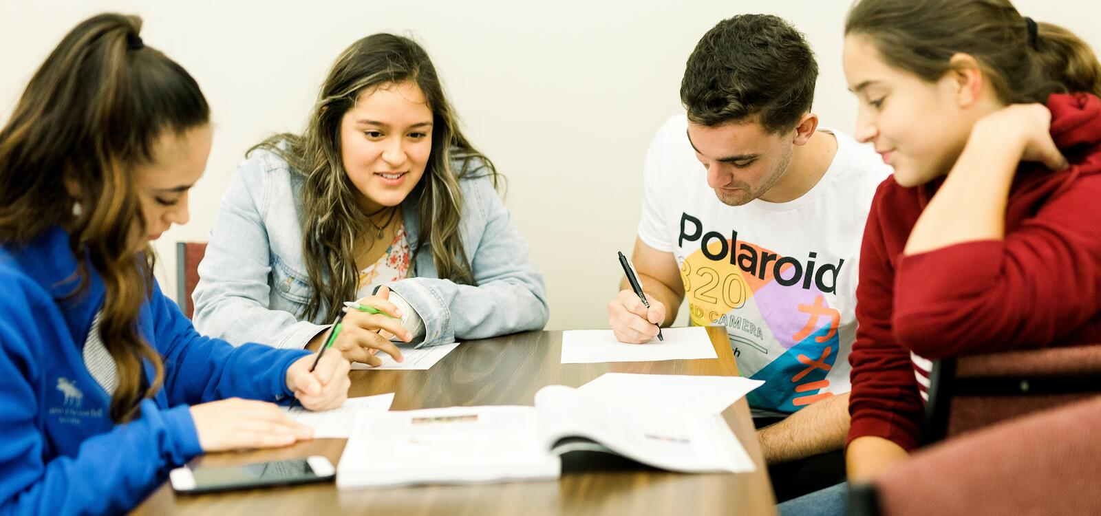 A group of four students sit at a rectangular table as they take notes from a textbook