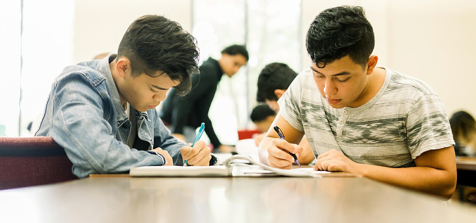 Two male students sit at a rectangle table taking notes from the same textbook