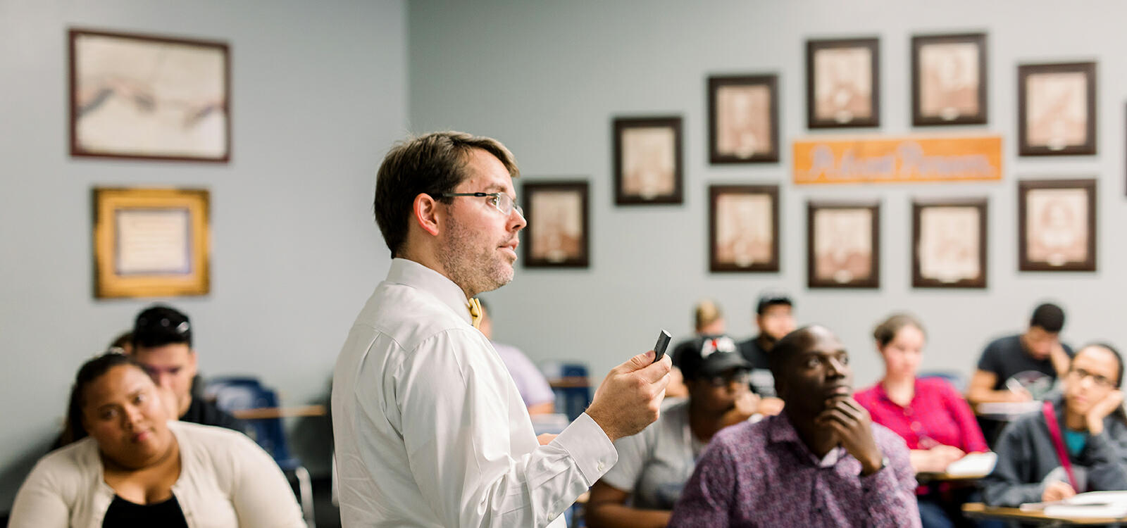 Dr. Michael Campbell, dressed in a white button up and yellow bow tie, stands in front of his class with a clicker in his hand