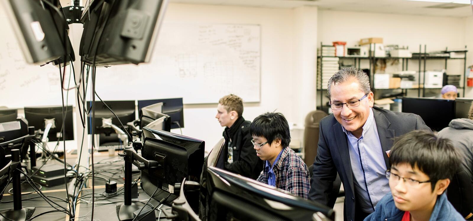 In a classroom filled with computers, a professor smiles as he looks over his student's computer screen